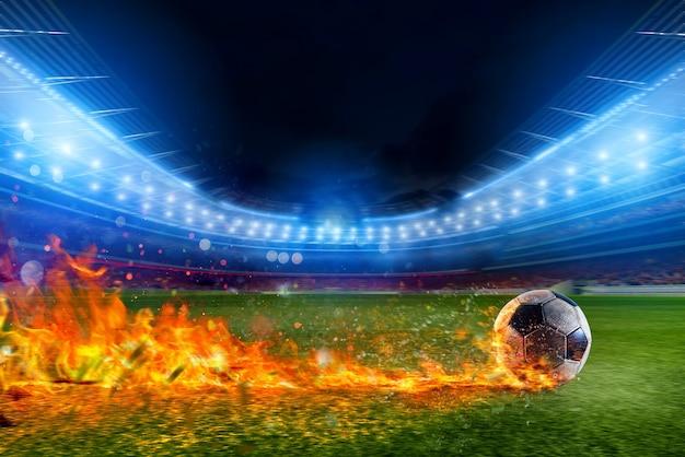 Пылающий футбольный мяч быстро летит на поле стадиона