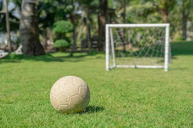 Футбольный мяч в траве перед стойкой ворот. футбольный мяч на зеленой траве детской площадки.