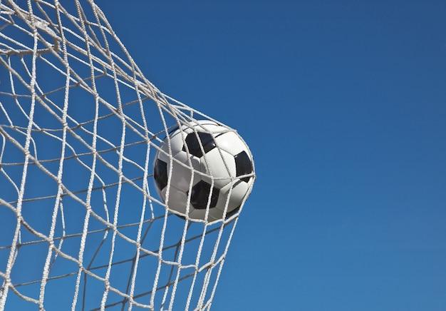 ゴールのネットでサッカーボール。サッカーのコンセプト