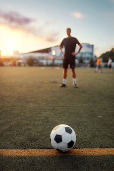 Soccer ball on line, player on the field on background. footballer on outdoor stadium, workout before game, football training
