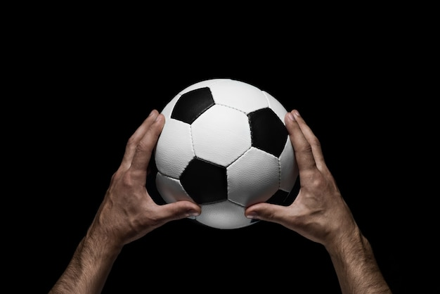 Soccer ball in male hands on a black
