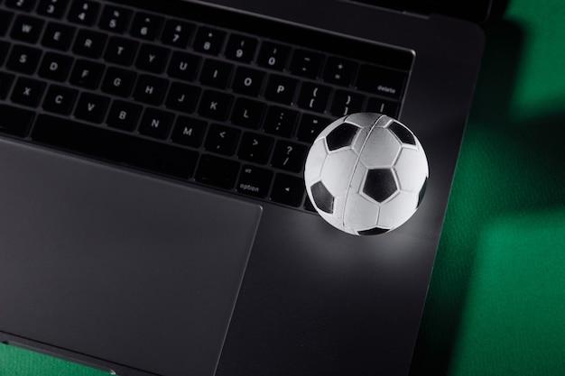 노트북의 키보드에 축구 공입니다. 스포츠, 도박, 돈 승리 개념