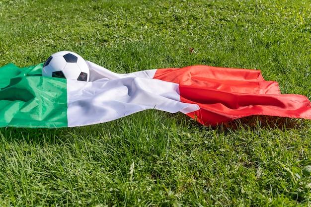 푸른 잔디 유럽 챔피언에 바람에 펄럭이는 이탈리아 국기의 배경에 축구공