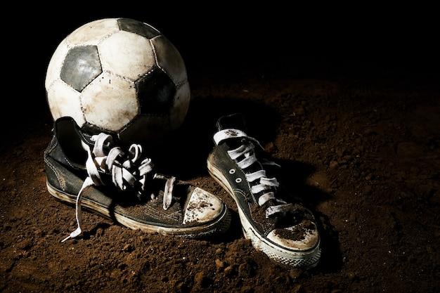 暗い表面の地面にサッカーボール