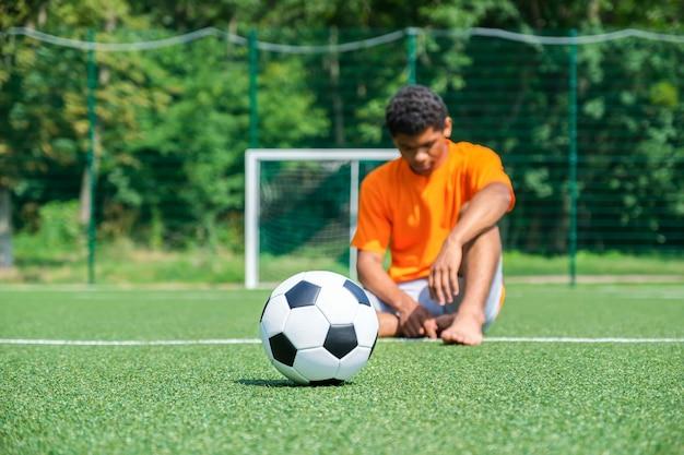 축구 골에 반대하는 야외 운동장에 있는 축구공과 운동장에 앉아 있는 슬픈 아프리카계 미국인 패자