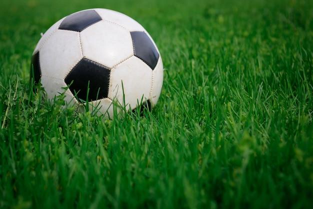 日当たりの良い夏の日に芝生の上のサッカーボール、クローズアップ。緑の芝生に白と黒のボール、コピースペース。アクティブレクリエーション、自然のスポーツエンターテイメントのコンセプトです。