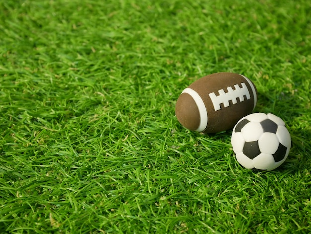 Soccer ball and rugby ball on green grass field