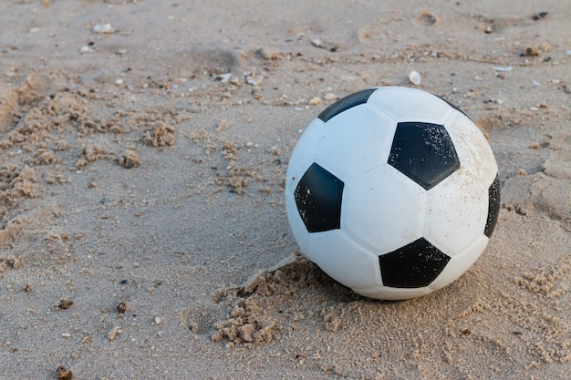 Soccer ball on the sand background