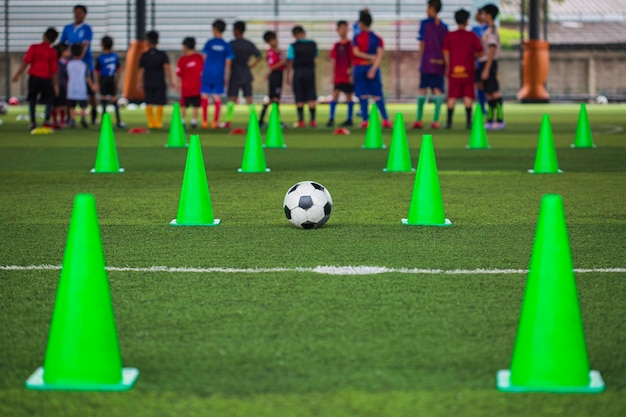 Soccer ball tactics cone on grass field with for training background training children in soccer