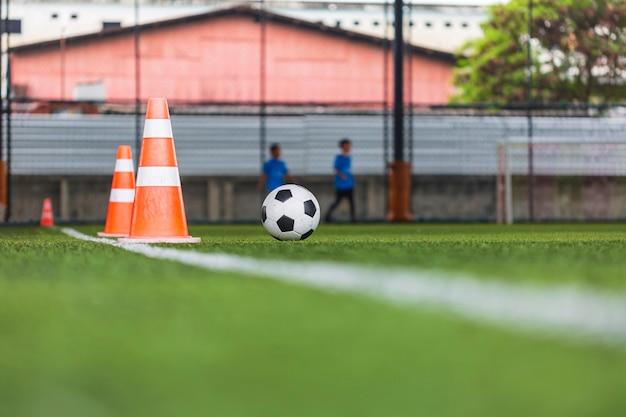 サッカーボールの戦術は、背景を訓練するための芝生のフィールドにコーンサッカーで子供たちを訓練する
