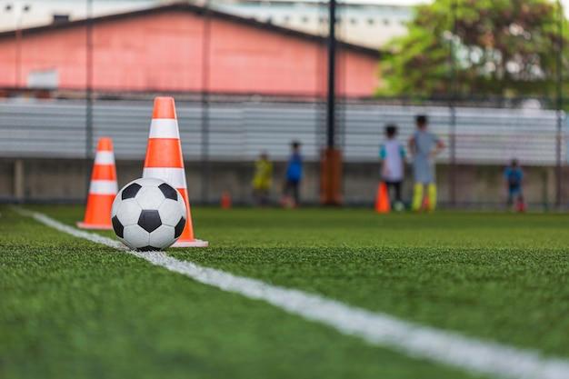 サッカーボールの戦術は、背景を訓練するために芝生のフィールドにコーンサッカーで子供たちを訓練する