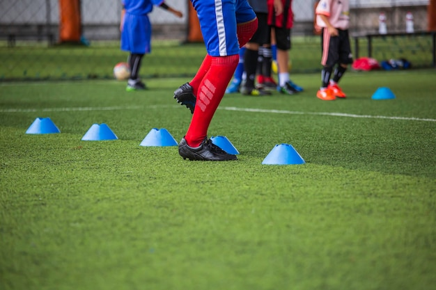 Soccer ball tactics on grass field with barrier for training children jump skill in soccer academy