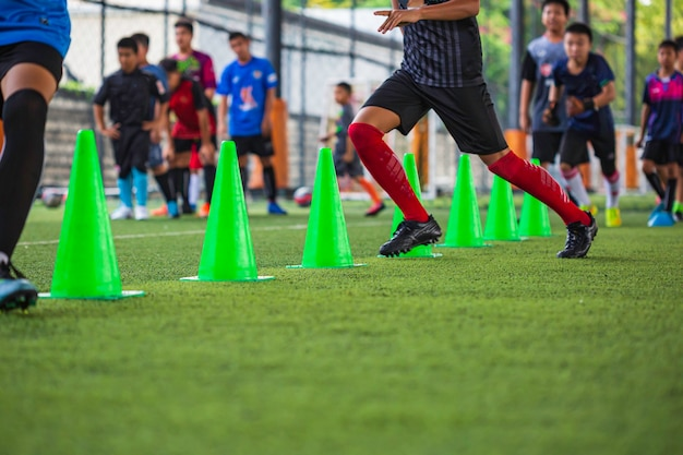 Soccer ball tactics on grass field with cone  for training children running skill in soccer academy