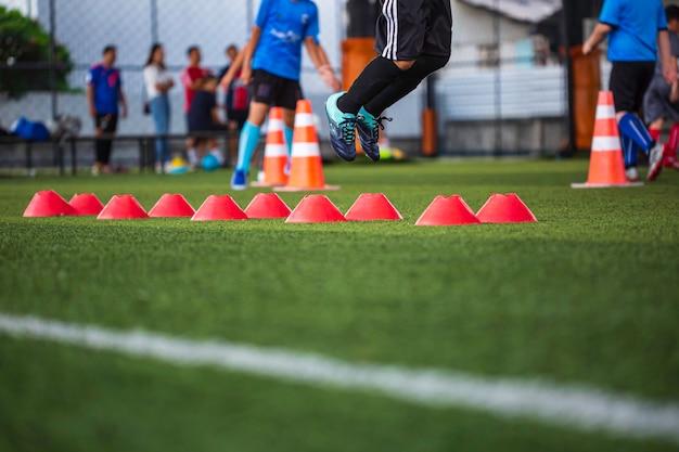 サッカーアカデミーで子供たちのジャンプスキルを訓練するためのバリアコーンを備えた芝生のフィールドでのサッカーボールの戦術