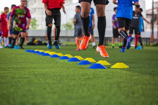축구 아카데미에서 어린이 점프 기술을 훈련하기 위한 장벽 콘이 있는 잔디 필드의 축구공 전술