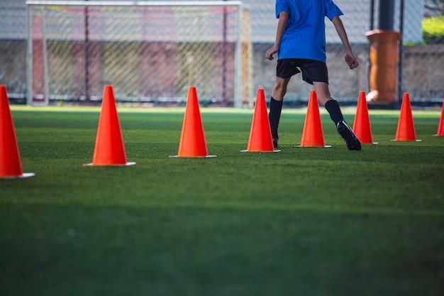 サッカーアカデミーで子供たちのジャンプスキルを訓練するための障壁を持つ芝生のフィールドでのサッカーボールの戦術