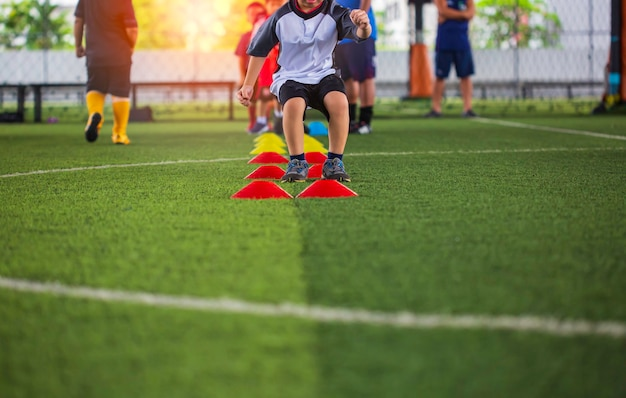 축구 아카데미에서 어린이 점프 기술 훈련을 위한 장벽이 있는 잔디 필드의 축구공 전술