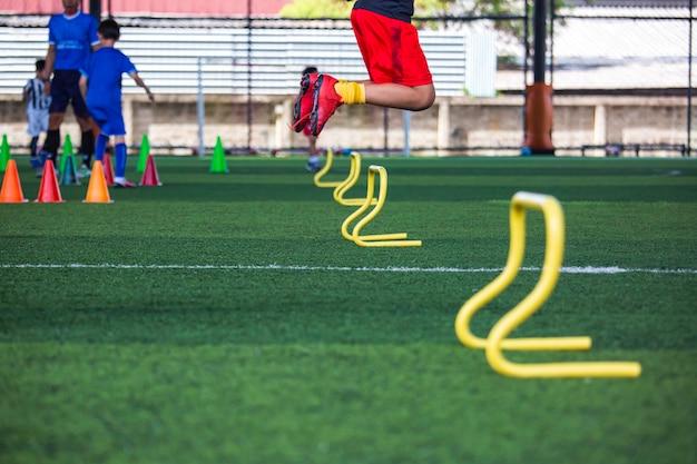 축구 아카데미에서 어린이 점프 기술을 훈련하기 위한 장벽이 있는 잔디밭에서의 축구공 전술