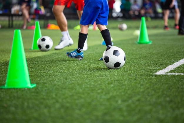 훈련 배경을 위한 콘이 있는 잔디 필드에서 축구공 전술 축구 아카데미에서 어린이 훈련