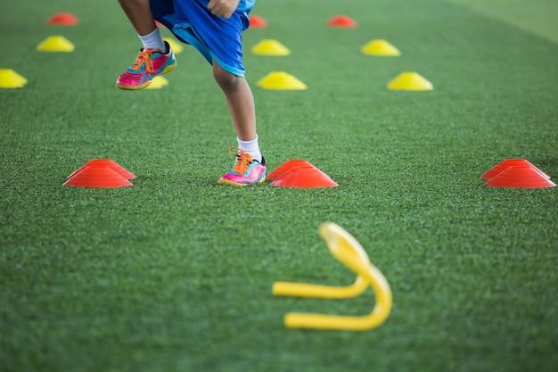 축구 아카데미에서 어린이 점프 기술을 훈련하기 위한 콘이 있는 잔디 필드의 축구공 전술