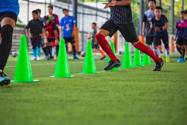 축구 아카데미에서 기술을 실행하는 어린이 훈련을 위한 콘이 있는 잔디 필드의 축구공 전술
