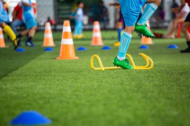 バックグラウンドでタイを訓練するためのコーンジャンプを備えた芝生のフィールドでのサッカーボールの戦術サッカーアカデミーで子供たちを訓練する