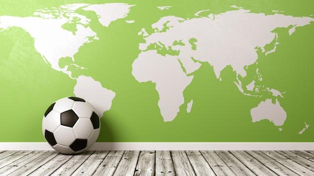 Футбольный мяч с зеленой картой мира на деревянном полу у стены