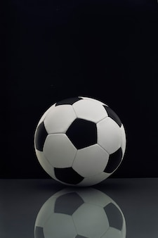 Soccer ball with reflection on the table on dark