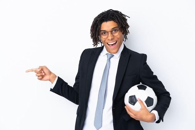Soccer coach over isolated white wall surprised and pointing finger to the side