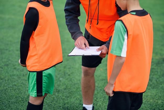 サッカーのコーチは、トレーニングで選手にサッカーの試合の戦略を示します。
