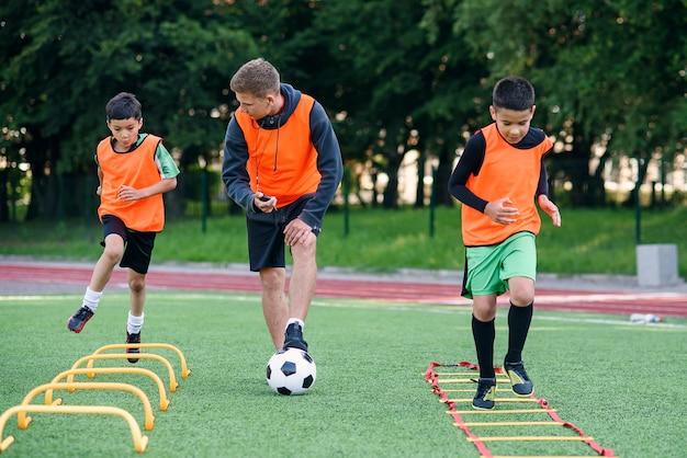 축구 코치는 장애물을 극복하고 달리기 운동을하는 동공을 지켜보고 있습니다.