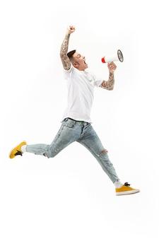 白い背景にジャンプするサッカーファン。オレンジ色のスタジオで分離されたメガホンを持つサッカーファンとしての若い男。サポートコンセプト。