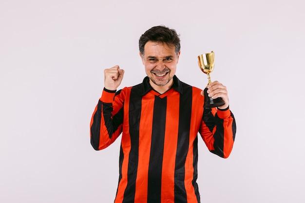 黒と赤のストライプのジャージを身に着けているサッカーファンは、彼の拳を握りしめ、白い背景に勝者のトロフィーを保持します