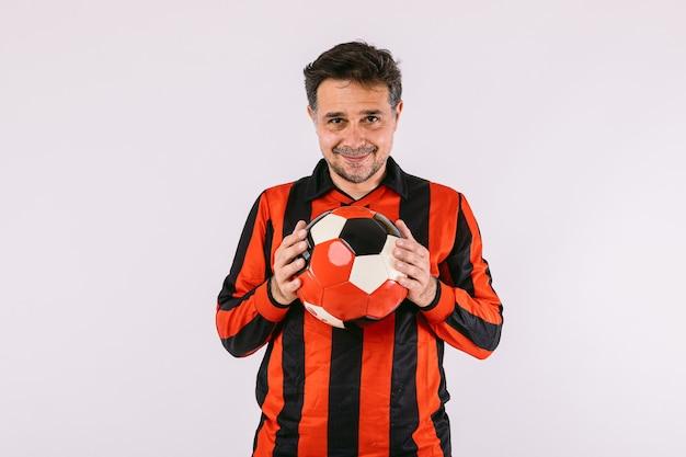 黒と赤のストライプのジャージを身に着けているサッカーファンは、白い背景の上の彼の手でボールを保持します。