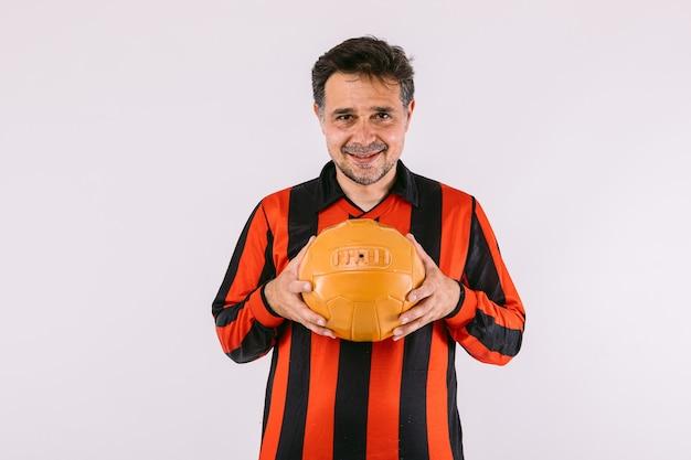 黒と赤のストライプのジャージを着て、白い背景の上の彼の手でレトロなボールを保持しているサッカーファン