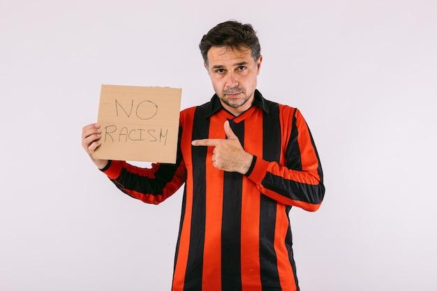 黒と赤のストライプのジャージを着て、白い背景に「人種差別なし」と書かれた看板を持っているサッカーファン