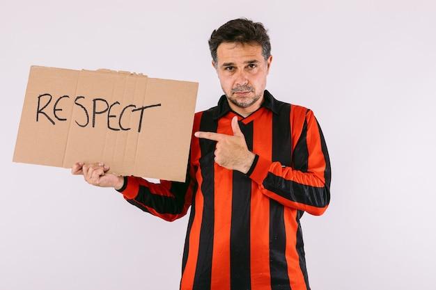黒と赤のストライプのジャージを着て、白い背景に「リスペクト」と書かれた看板を持っているサッカーファン