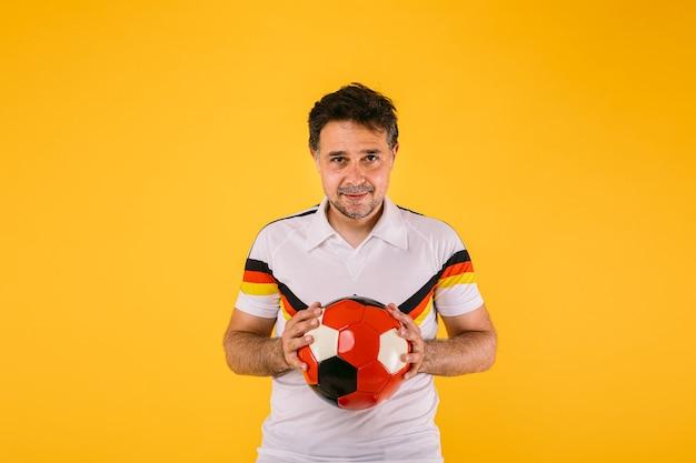 黒、赤、黄色のストライプの白いtシャツを着ているサッカーファンは、彼の手でボールを保持します