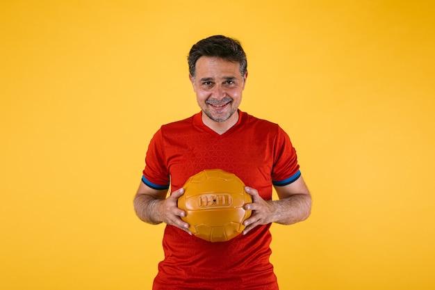彼の手に赤いジャージとレトロなボールを持つサッカーファン