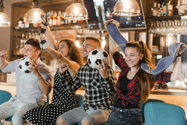 Soccer fans sitting in bar celebrating victory