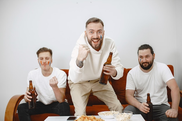 거실 소파에 앉아 맥주를 마시는 축구 팬들