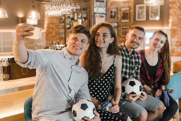 Soccer fans sitting in row taking selfie at bar