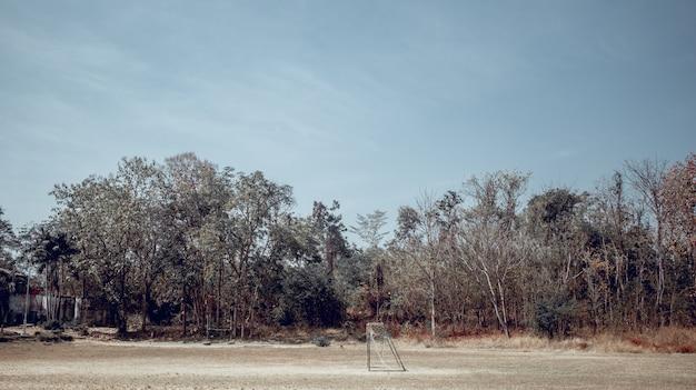 Футбольное поле и старая цель футбола на спортивной площадке деревни в летнем дне., футбольное поле на городской школе. спортивная концепция.