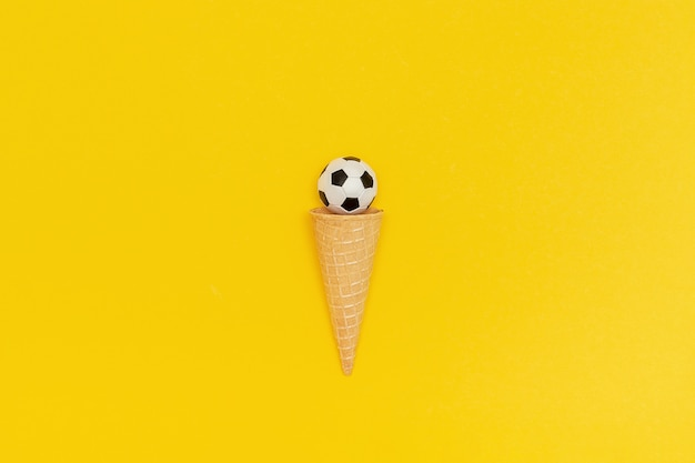 Soccer or football ball in ice cream cone on yellow background.
