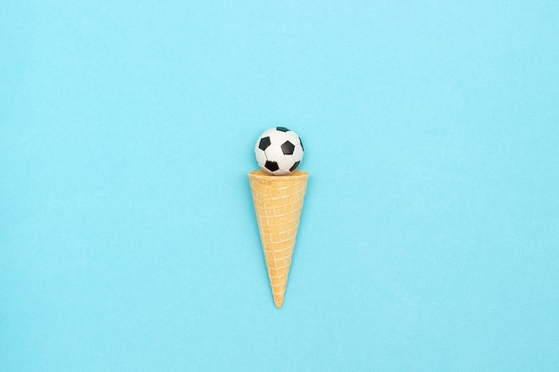 Soccer or football ball in ice cream waffle cone. concept sports entertainment.