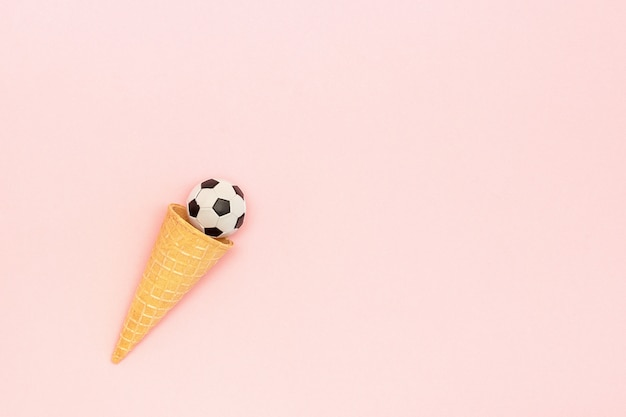 Soccer or football ball in ice cream waffle cone on pink background in minimal style.