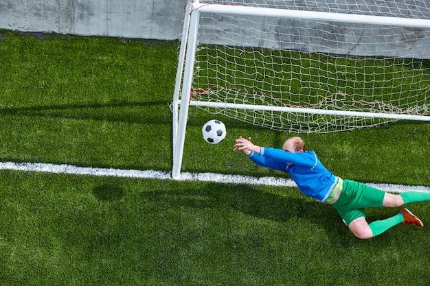 Футболист футбольный вратарь делает дайвинг экономией на грин филд