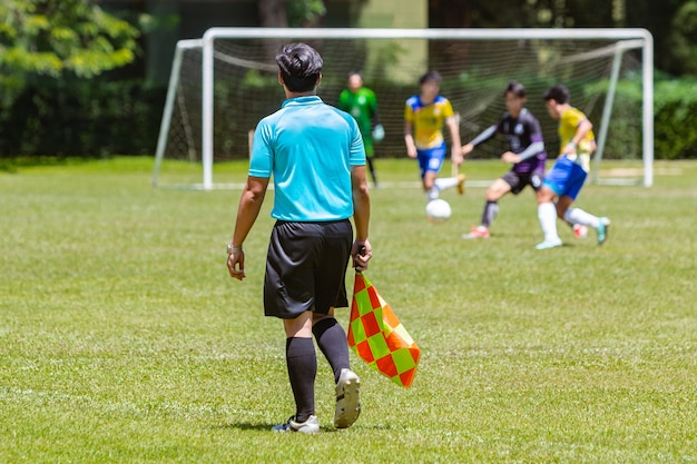 Soccer or football lineman referee watching a boy youth game