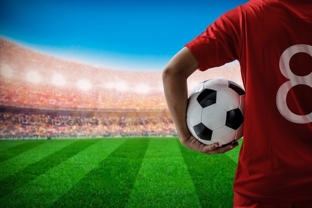 Soccer football player no.8 in red team concept holding soccer ball in the stadium