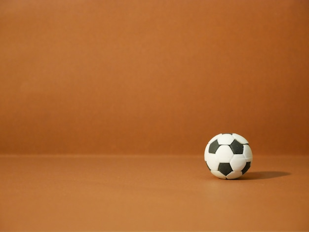 Soccer football with copy space on brown background.